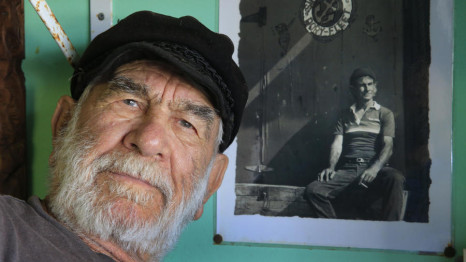 Fishing family patriarch Stratos Voyatzis is shown with a photo of his younger self at the Dory Fleet market.