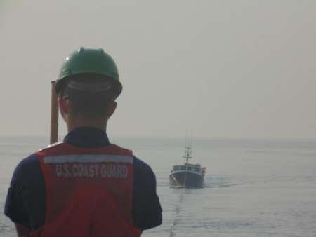 crew member aboard Coast Guard Cutter Escanaba stands tow watch over the fishing vessel Danny Boy