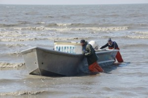 A pair of setnetters push their boat to shore in Cook Inlet in 2013.